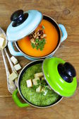 Two kinds of cream soup (broccoli and pumpkin) in pot on wooden background — Stock Photo