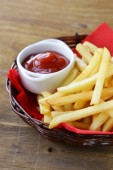 Traditional French fries with ketchup in a wicker basket — Stock Photo