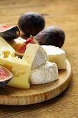 Cheeseboard with maasdam, camembert, cheddar cheese and figs — Stock Photo