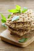 Dry flat bread crisps with herbs on a wooden board — Stock Photo