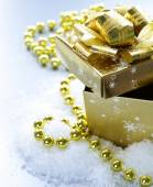 Golden gift box with beautiful ribbon in the snow, christmas still life — Stock Photo