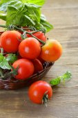 Branch of fresh organic  tomatoes with green basil on wooden background — Stock Photo