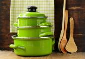 Set of metal green pots cookware on a wooden background — Stock Photo