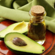 Oil of avocado and fresh fruit on wooden table — Stockfoto #54434273