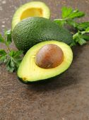 Fresh organic ripe avocado with leaves of parsley — Stock Photo