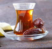 Turkish tea in traditional glass with sweet dates — Stock Photo