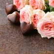 Chocolate candy in the shape of hearts and pink roses for Valentine's day holiday — Zdjęcie stockowe #58264603