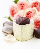 Čokoládové bonbóny ve tvaru srdce a růžové růže na Valentýna svátek — Stock fotografie