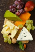 Cheeseboard with different types of cheese and grapes — Photo