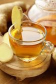 Beverage tea with ginger and fresh root on a wooden background — Stock Photo