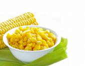 Canned corn in a bowl and fresh cobs — Stock Photo