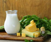 Milk and cheese on a wooden table, rustic style — Stock Photo