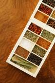 Set of different spices (pepper, salt, turmeric, bay leaves, chili, herbs) in a wooden box — Stock Photo
