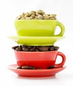 Green and black coffee beans in cup on a white background — Stock Photo