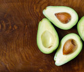 Ripe organic avocado cut in half on a wooden background — Stock Photo