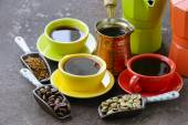 Green, black coffee beans and different utensils for boiling coffee (grinder, kettle, cezve) — Stock Photo