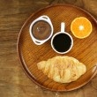 Breakfast serving funny face on the plate (croissant, chocolate spread, orange and coffee) — Stock Photo #72868083
