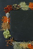Different spices on a black background (paprika, turmeric, pepper, aniseed, cinnamon, saffron) — Stock Photo