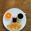 Breakfast serving funny face on the plate (jam, croissant, orange and coffee) — Stock Photo #73057199