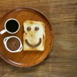 Breakfast serving funny face on the plate (toast, chocolate spread and coffee) — Stock Photo #73057581