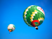 Colorful flying balloons in blue sky — Stock Photo