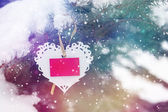 Snowy background with white Valentines lace heart with card — Stock Photo