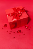 Gift box with bow and hearts on the red background — Stockfoto