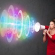 Young girl yells into a loudspeaker and colorful energy beam com — Stock Photo #51949627