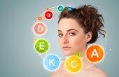 Hübsche junge mädchen mit bunten vitamin-icons und symbole — Stockfoto