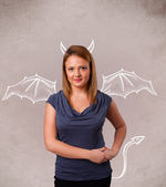 Young girl with devil horns and wings drawing — Stock Photo