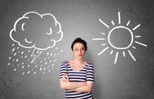 Woman standing between a sun and a rain drawing — Stock Photo