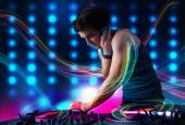 Young Dj mixing records with colorful lights — Stock Photo