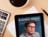 Tablet pc mostrando revista en pantalla con una taza de café en una d — Foto de Stock