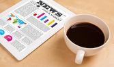 Tablet pc muestra noticias en pantalla con una taza de café en un escritorio — Foto de Stock