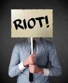 Businessman holding a protest sign — Stock Photo