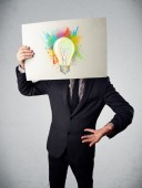 Businessman holding a cardboard with paint splashes and lightbul — Stock Photo