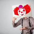 Businessman holding a cardboard with a clown on it in front of h — Stock Photo #55464637