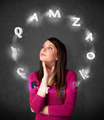 Young woman thinking with letter circulation around her head — Stock Photo
