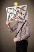 Businessman holding a paper with a labyrinth on it in front of h — Stock Photo