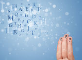 Happy smiley fingers looking at mixture of bokeh letters — Stock Photo