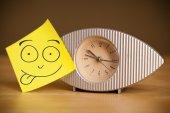 Po to Uwaga z uśmiechniętą twarz naklejane na zegarze — Zdjęcie stockowe