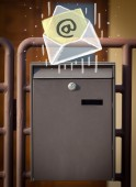 Envelope with email sign dropping into mailbox — Stock Photo