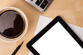 Tablet pc with empty space and a cup of coffee on a desk — Stock Photo