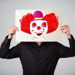 Businessman holding a cardboard with a clown on it in front of h — Stock Photo #57233809
