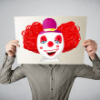 Businessman holding a cardboard with a clown on it in front of h — Stock Photo #57783939