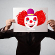 Businessman holding a cardboard with a clown on it in front of h — Stock Photo #58324279