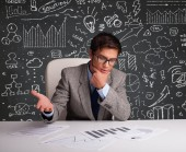 Businessman sitting at desk with business scheme and icons — Stock Photo