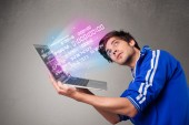 Casual man holding laptop with exploding data and numbers — Stock Photo