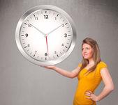 Attraktiv dam som håller en stor klocka — Stockfoto
