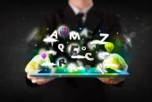Young person showing tablet with abstract letters and sky — Stock Photo